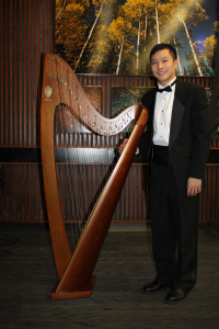 Justin standing beside harp - original enhanced