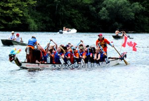 Dragon boat in a race with Justin at back steering